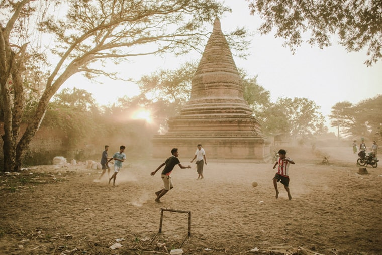 kids playing football barefoot on the sands amongs the pagodas in bagan myanmar